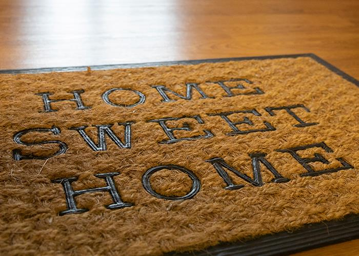 """Picture of welcome mat with """"Home Sweet Home"""" Please use the login button in the gold bar above."""